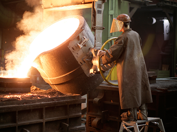 A foundry mechanic pours liquid iron in a mould